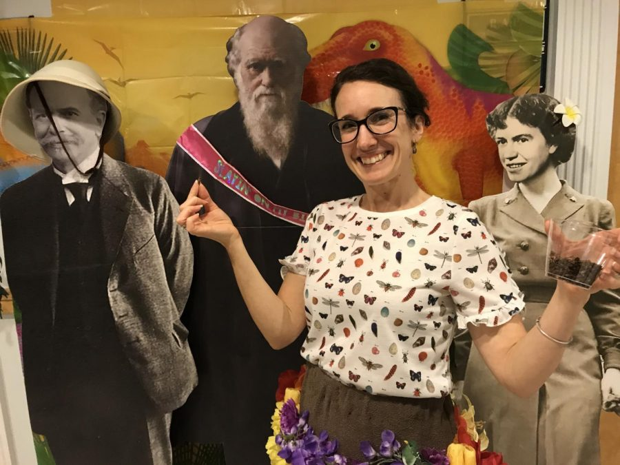 Dr. Michaela Howells, standing amongst cardboard cutouts of her peers and Darwin himself, holds a cup of the insects she brought for attendees to snack on during Darwin Day Wednesday night in Cameron Hall.