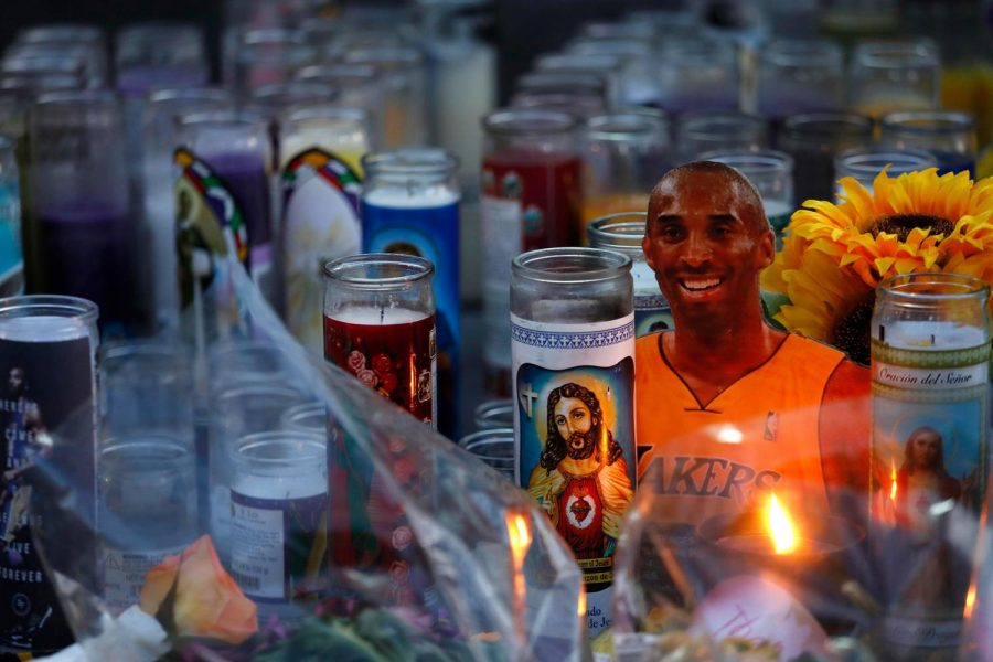 A figure of Kobe Bryant peers above candles at a memorial for the Lakers star at LA Live in downtown Los Angeles on Jan. 29, 2020.