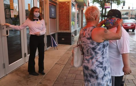 Emerson Becker, 20, holds the door for two customers as they put on their masks before entering Classic Cinemas York Theatre in Elmhurst after reopening on June 26, 2020.  USA