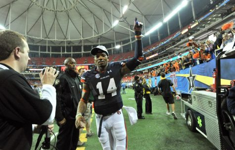 Auburn quarterback Nick Marshall (14) leaves the field as fans celebrate a 59-42 victory against Missouri in the SEC Championship game at the Georgia Dome in Atlanta, Saturday, Dec. 7, 2013.