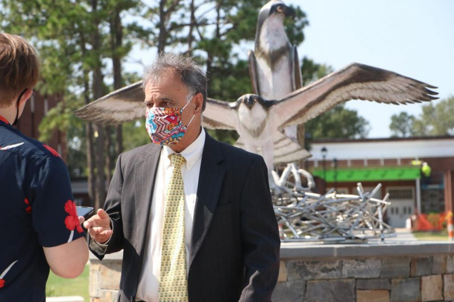 UNCW Chancellor Jose V. Sartarelli answering questions front of the new sculpture.
