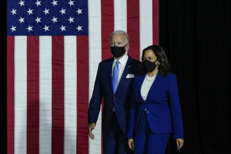 Democratic presidential nominee former Vice President Joe Biden, left, and running mate Sen. Kamala Harris (D-CA) take the stage to deliver remarks at Alexis Dupont High School in Wilmington, Delaware, on Wednesday, Aug. 12, 2020. The pair will be regularly tested for coronavirus as campaigning intensifies in the weeks before the election. (Drew Angerer/Getty Images/TNS)