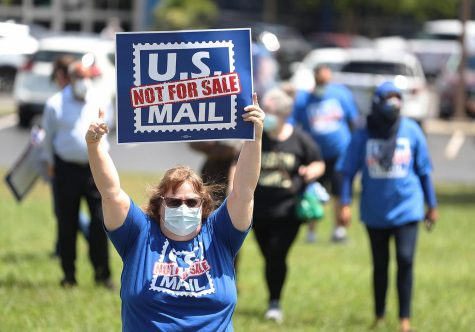 Postal workers hold signs as U.S. Rep. Val Demings speaks at a post office at Kirkman Road in Orlando on Tuesday, Aug. 18, 2020. (Stephen M. Dowell/Orlando Sentinel/TNS)