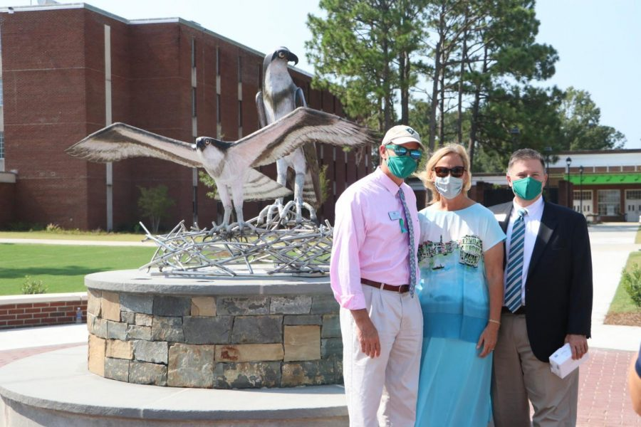 Associate Vice Chancellor and Dean of Students Mike Walker, Susan Vanecek, wife of the late Vice Chancellor for Student Affairs Pat Leonard, and Interim Vice Chancellor for Student Affairs Brian Victor  in front of the new sculpture.