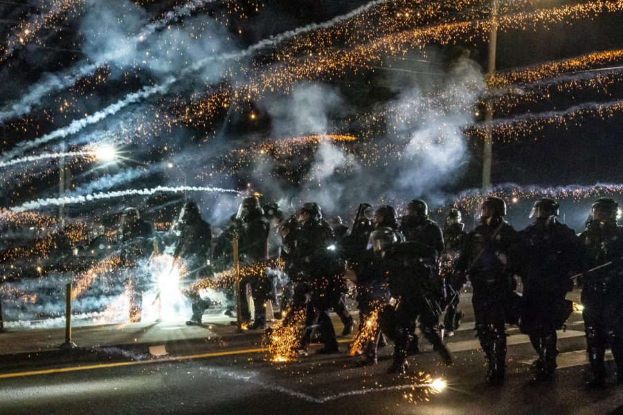 Oregon State Troopers and Portland police advance through tear gas and fire works while dispersing a protest against police brutality and racial injustice on September 5, 2020 in Portland, Oregon. Portland has seen nightly protests for the past 100 days following the death of George Floyd in police custody. (Nathan Howard/Getty Images/TNS)