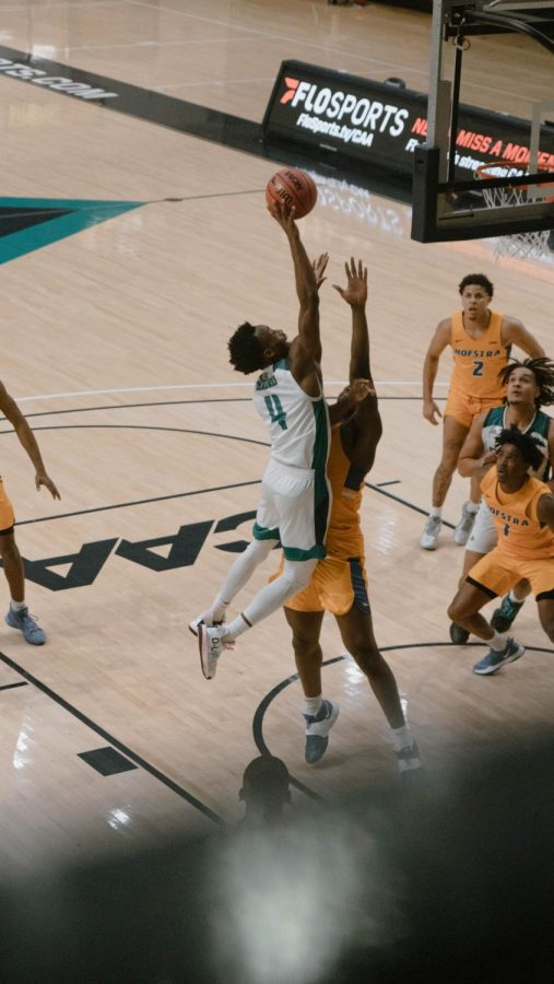Mike Okauru drives to the basket during UNCW's matchup against Hofstra on Jan. 30, 2021
