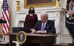President Joe Biden signs an executive order after speaking during an event on his administration's COVID-19 response with Vice President Kamala Harris, left, in the State Dining Room of the White House in Washington, D.C., on Thursday, Jan. 21, 2021.  Photo by Irfan Khan - TNS