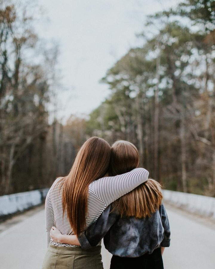 Two girl best friends hugging each other facing opposite direction.