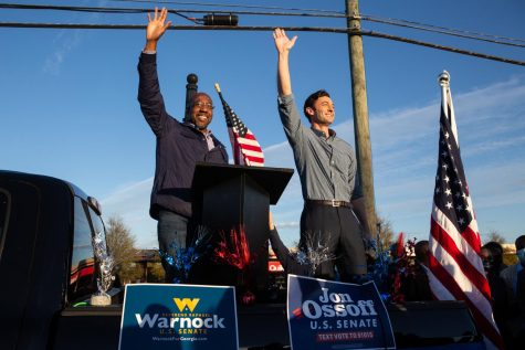 Democratic U.S. Senate candidates Jon Ossoff, right, and Raphael Warnock of Georgia wave to supporters during a rally on November 15, 2020, in Marietta, Georgia.