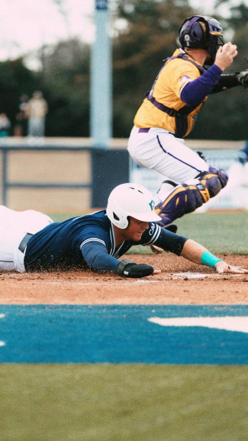 Cole Weiss sliding across home plate during UNCW's matchup with ECU on Mar. 17, 2021.