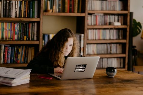 Young teen doing schoolwork at home after schools close due to the Coronavirus.