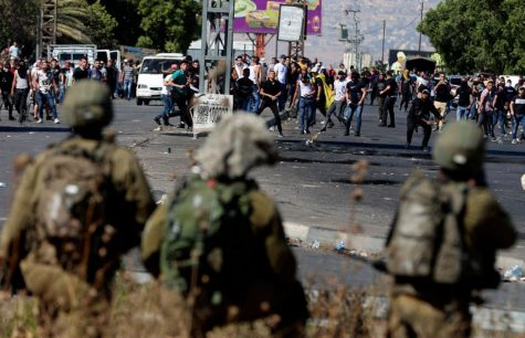 Palestinian protesters clash with Israeli security forces at the Hawara checkpoint south of Nablus city, in the occupied West Bank, on May 18, 2021. - Palestinians across the West Bank and in east Jerusalem and Arab districts in Israel were largely adhering to a general strike called in support of those under bombardment in Gaza, which led to violent clashes throughout the territories.