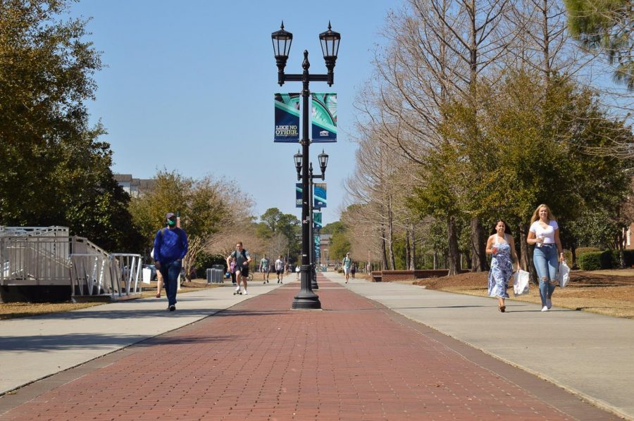 Students walking on campus with and without face masks.