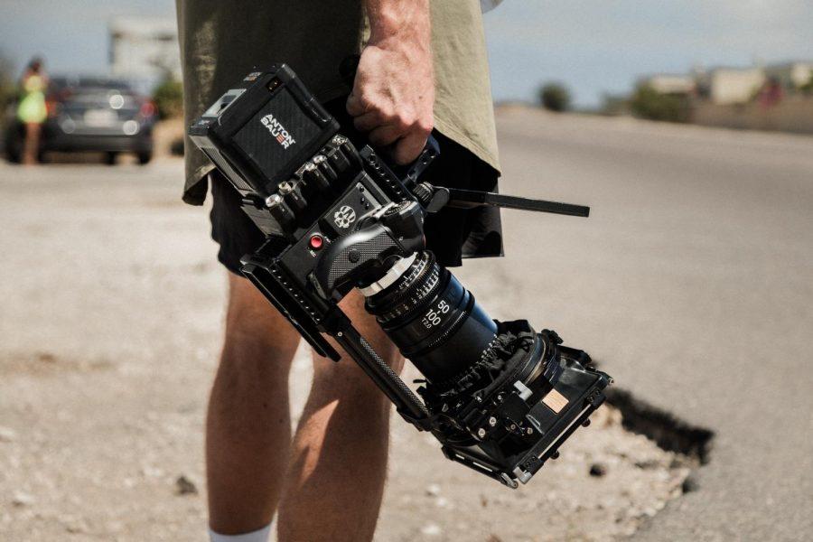 A man holds a film camera.