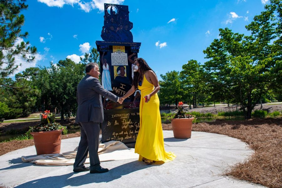 """The artist Dare Coulter shakes hands with Chancellor Sartarelli in front of her piece, """"Because It"""