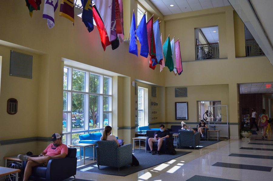 Students sit inside the Fisher Student Center to do work.